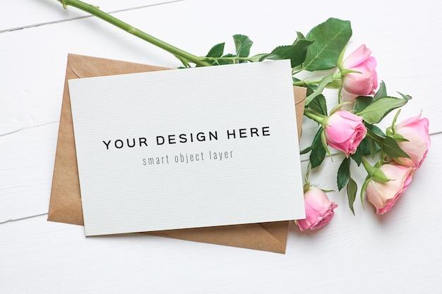 Maquete de cartão comemorativo com envelope e flores de rosas frescas