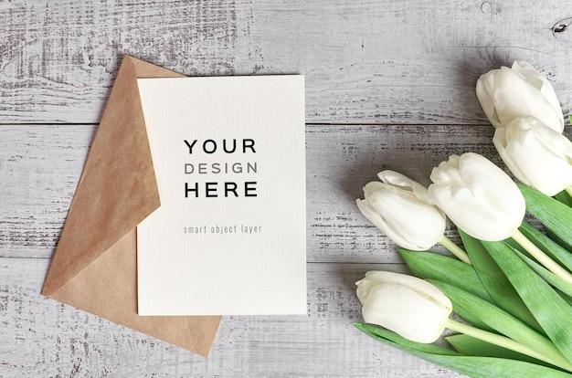 Maquete de cartão comemorativo com envelope e flores de tulipa