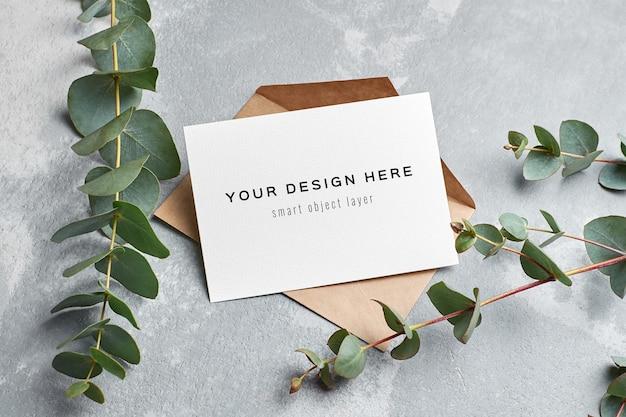 Maquete de cartão comemorativo com envelope e galhos de eucalipto em cinza