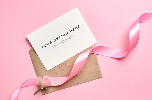 Maquete de cartão comemorativo com envelope, fita rosa e flor rosa