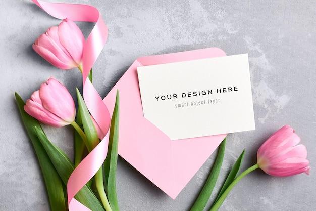 Maquete de cartão comemorativo com envelope rosa e buquê de flores de tulipa