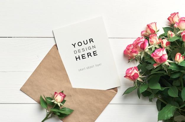 Maquete de cartão comemorativo com flores de envelope e rosas em fundo branco de madeira