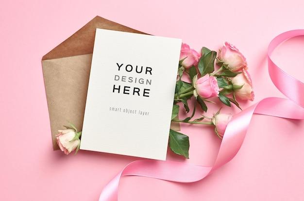 Maquete de cartão comemorativo com flores de envelope e rosas em fundo rosa