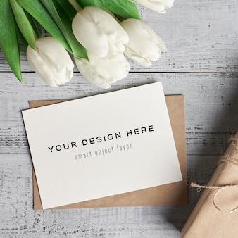 Maquete de cartão comemorativo com flores de tulipa e caixa de presente