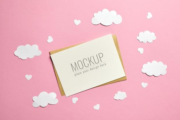 Maquete de cartão comemorativo com nuvens de papel e corações na superfície rosa