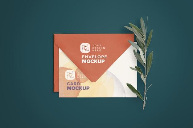 Maquete de cartão de 5x7 polegadas dobrado em um envelope com galho de oliveira