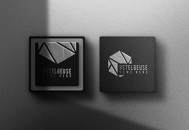Maquete de cartão de caixa preta com logotipo em relevo de folha de metal prateado