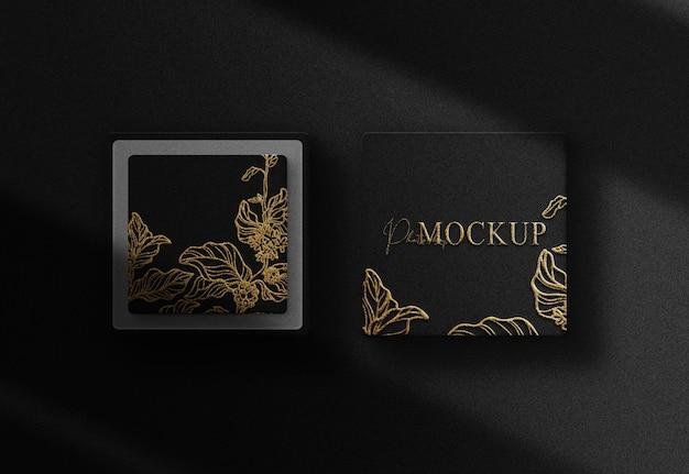 Maquete de cartão de caixa preta com logotipo em relevo de folha de ouro