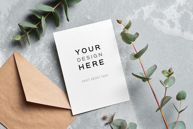 Maquete de cartão de convite de casamento com envelope e galho de eucalipto