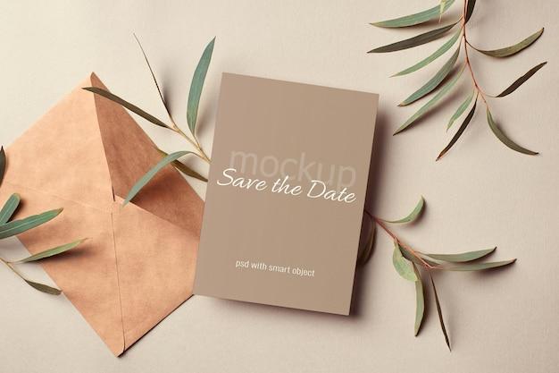 Maquete de cartão de convite de casamento com envelope e galhos de eucalipto