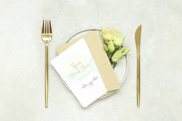 Maquete de cartão de convite de casamento em talheres de prato e ouro