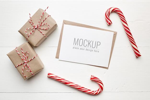 Maquete de cartão de desejo de natal com caixas de presente e bastões de doces