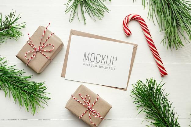 Maquete de cartão de desejos de natal com caixas de presente, bengala e galhos de pinheiro