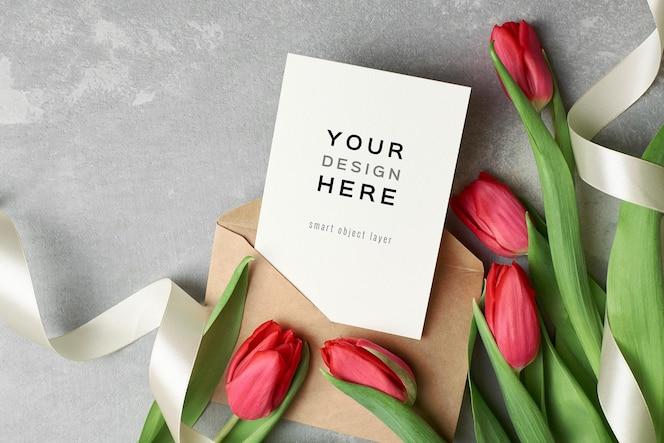 Maquete de cartão de dia das mulheres com envelope e flores de tulipa vermelha