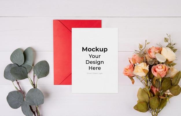 Maquete de cartão de dia dos namorados, carta e flores na mesa de madeira
