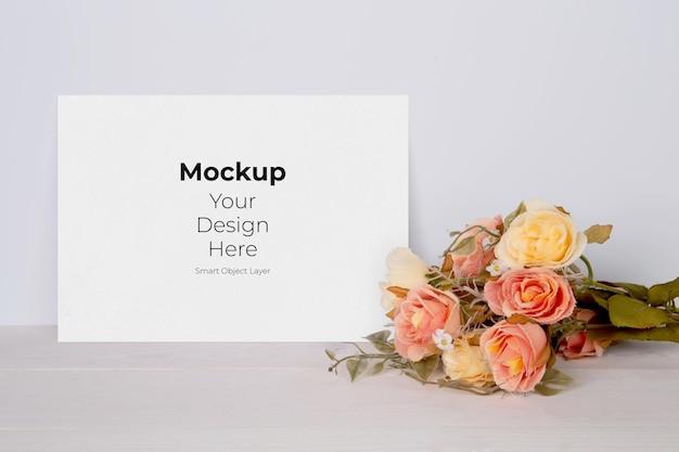 Maquete de cartão de dia dos namorados vazio e flores na mesa de madeira