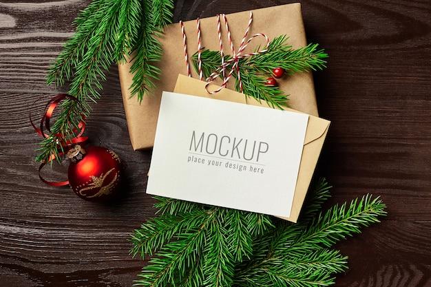 Maquete de cartão de felicitações com caixa de presente, bola vermelha de natal e galhos de pinheiro na mesa de madeira