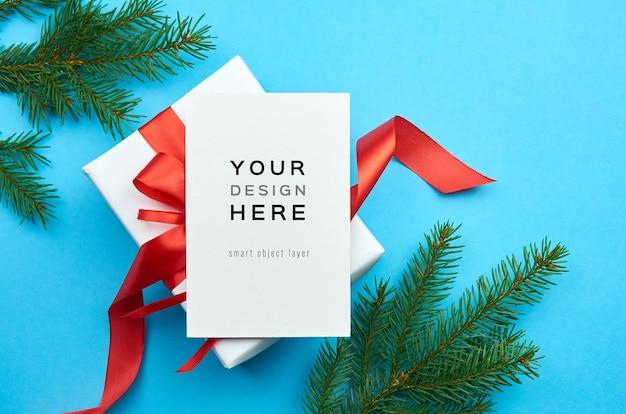 Maquete de cartão de felicitações com caixa de presente de natal e galhos de pinheiro