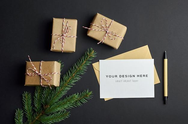 Maquete de cartão de felicitações com caixas de presente de natal e galhos de pinheiros escuros