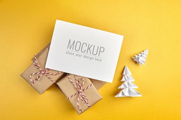 Maquete de cartão de felicitações com caixas de presente e árvores de natal de papel com fundo dourado