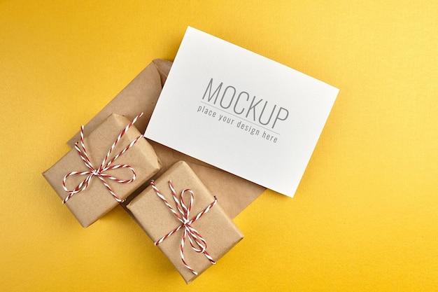 Maquete de cartão de felicitações com caixas de presente em fundo de papel dourado