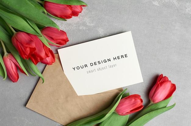 Maquete de cartão de felicitações com envelope e buquê de flores de tulipa vermelha em fundo cinza