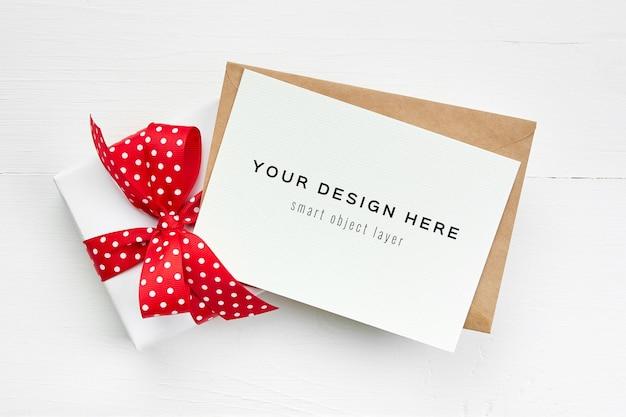 Maquete de cartão de felicitações com envelope e caixa de presente com fita vermelha em branco