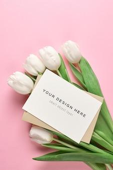 Maquete de cartão de felicitações com envelope e flores de tulipa branca em fundo rosa