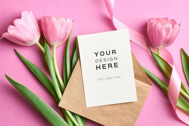 Maquete de cartão de felicitações com envelope e flores de tulipa rosa