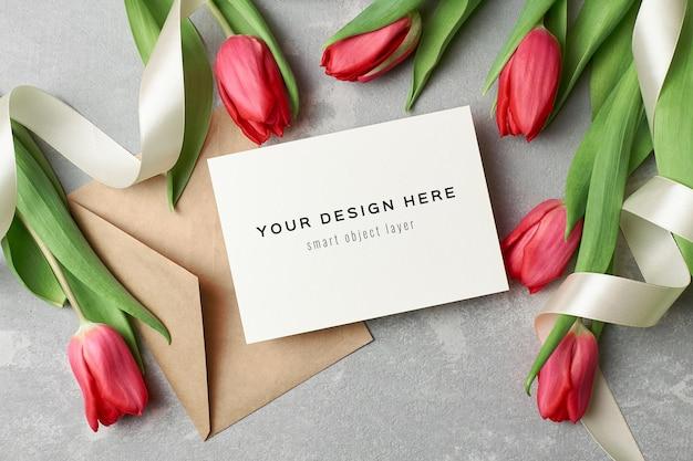 Maquete de cartão de felicitações com envelope e flores de tulipa vermelha