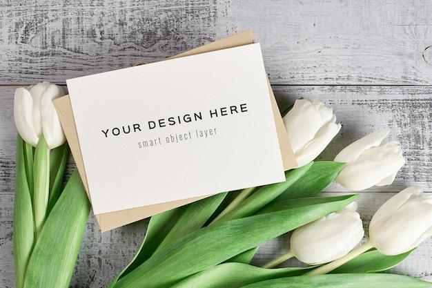 Maquete de cartão de felicitações com envelope e flores tulipa em fundo de madeira