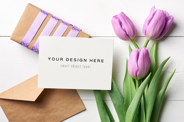 Maquete de cartão de felicitações com flores de tulipa, envelope e caixa de presente com fundo de madeira