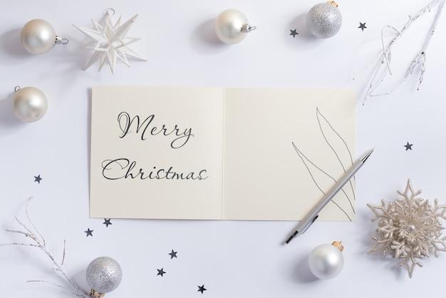 Maquete de cartão de feliz natal com bolas de natal brancas