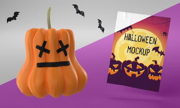 Maquete de cartão de halloween ao lado de uma abóbora assustadora