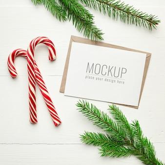 Maquete de cartão de natal com bastões de doces e galhos de pinheiros