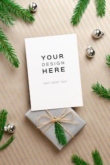 Maquete de cartão de natal com caixa de presente, decorações festivas e galhos de pinheiros
