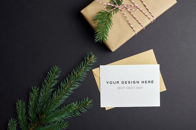 Maquete de cartão de natal com caixa de presente e galhos de árvore de abeto no preto
