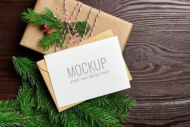 Maquete de cartão de natal com caixa de presente e galhos de pinheiro em fundo de madeira