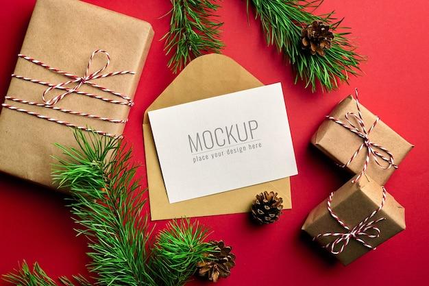 Maquete de cartão de natal com caixas de presente e galhos de pinheiros