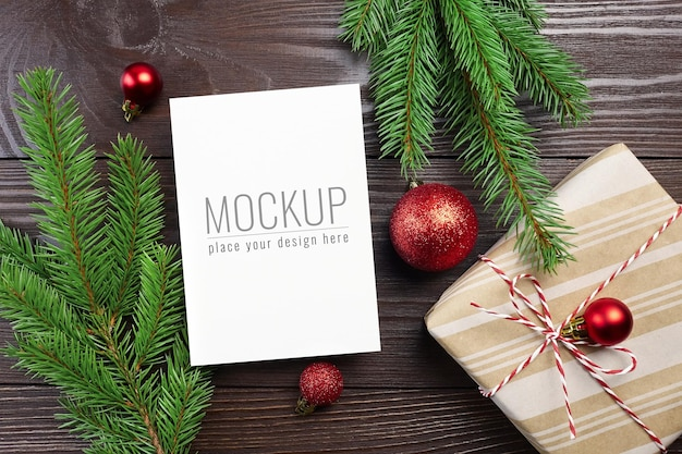 Maquete de cartão de natal com decorações festivas de bolas vermelhas e caixa de presente