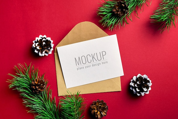 Maquete de cartão de natal com envelope e galhos de pinheiro com cones