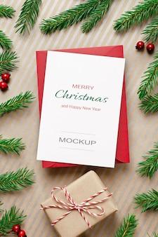 Maquete de cartão de natal com envelope vermelho, caixa de presente e galhos de pinheiros decorados