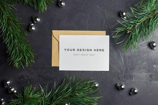 Maquete de cartão de natal com galhos de pinheiro e enfeites de bolas de prata no escuro