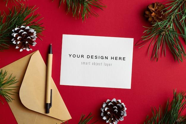 Maquete de cartão de natal com galhos de pinheiro verde no vermelho
