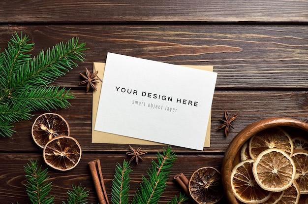 Maquete de cartão de natal com laranjas secas, especiarias e ramos de pinheiro