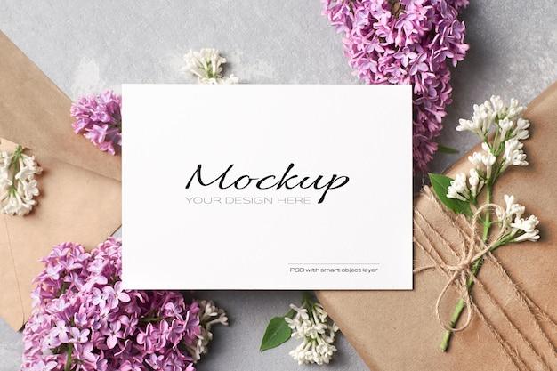 Maquete de cartão de saudação ou convite com caixa de presente, envelope e flores lilás