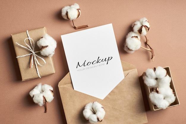 Maquete de cartão de saudação ou convite com envelope, caixa de presente e enfeites de flores de algodão