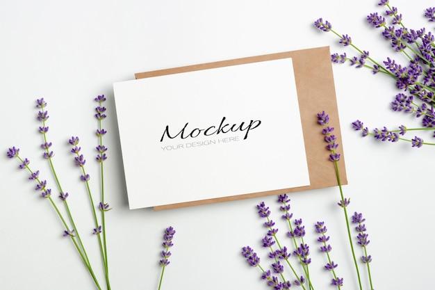 Maquete de cartão de saudação ou convite com envelope e flores frescas de lavanda em branco
