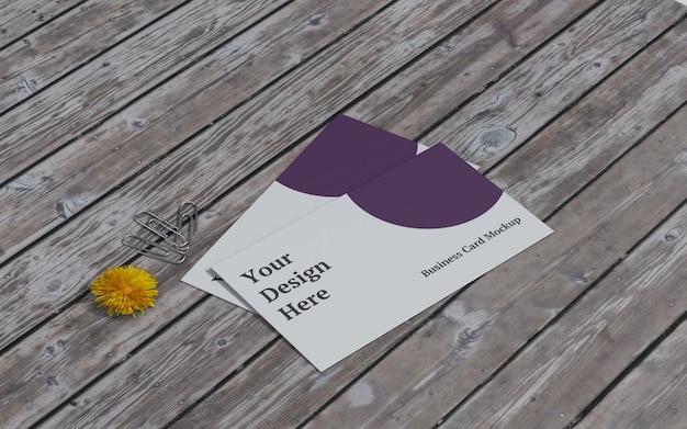Maquete de cartão de visita com flor amarela e clipe de papel à esquerda vista