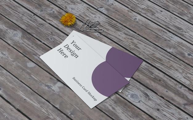 Maquete de cartão de visita com flor amarela e clipe de papel vista certa